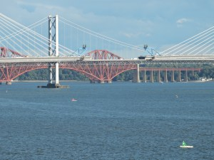 A new bridge across the Firth of Forth with the world's first steel bridge behind it.
