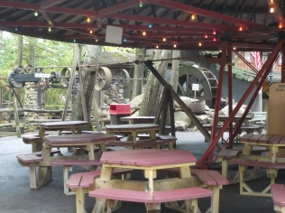 An old water mill powers the rotating roof over picnic tables.